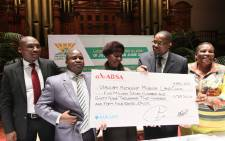 FILE: Deputy Minister for Rural Development and Land Reform Mcebisi Skwatsha (second right) hands over a cheque to the tenants of Verulam Mission in Durban at the City Hall. Picture: GCIS