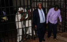 Zimbabwe's former Minister of Finance Ignatius Chombo (2nd R) leaves Harare Magistrates Court shackled to former Zanu-PF Youth League chairperson Kudzai Chipanga (R) after he was remanded in custody on fraud charges on 25 November 2017. Picture: AFP