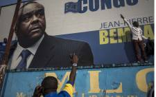FILE: Supporters of Jean-Pierre Bemba raise their hands as they stand in front of his picture in Kinshasa on 8 June 2018. Picture: AFP.