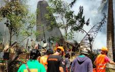 In this handout photo taken on July 4, 2021 and received from the Philippine military Joint Task Force-Sulu (JTF-Sulu), rescue workers arrive as smoke billows from the wreckage of a Philippine Airforce C-130 transport plane after it crashed near the airport in Jolo town, Sulu province on the southern island of Mindanao. Picture: AFP: