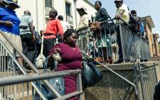 A woman with cash in hand walks past fellow bank customers queing to withdraw the new Zimbabwe currency in Harare on 12 November 2019. Picture: AFP