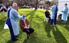 Interstate health workers from Adelaide in South Australia take a swab as people queue during COVID-19 coronavirus testing in a park in the Melbourne suburb of Brunswick West on July 2, 2020. Picture: AFP