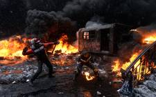 A protestor throws a molotov cocktail at riot police in the centre of Kiev on 22 January, 2014. AFP