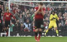 Liverpool's Brazilian goalkeeper Alisson Becker (R) reacts after Manchester United's English defender Chris Smalling (L) missed a chance during the English Premier League football match between Manchester United and Liverpool at Old Trafford in Manchester, north west England, on 24 February 2019. Picture: AFP