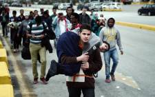 FILE: A Syrian man carries his disabled relative as they walk with other migrants and asylum seekers to find transportation to central Athens or continue towards the Greek-Macedonian border from the port of Piraeus. Picture: AFP