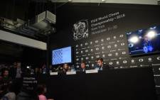 FIDE Press Officer Anastasia Karlovich, Chess grandmaster Sergey Karjakin and Reigning Chess Champion Magnus Carlsen speak at a press conference. Picture: Getty Images for Agon Limited/AFP.
