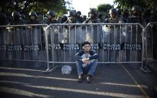 A supporter of opposition candidate Salvador Nasralla rests next to a group of Honduran military police after a march held on 3 December, 2017 in Tegucigalpa. Picture: AFP.