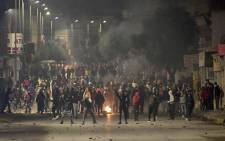 Protesters stand amidst fumes as they block a street during clashes with security forces in the Ettadhamen city suburb on the northwestern outskirts of Tunisia's capital Tunis on 18 January 2021, amidst a wave of nightly protests in the North African country. Picture: Fethi Belaid/AFP