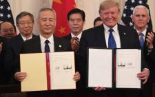 Chinese Vice Premier Liu He (left) and US President Donald Trump (right) display the signed trade agreement between the US and China in the East Room of the White House in Washington, DC, 15 January 2020. Picture: AFP