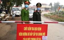 Vietnamese police wearing protective facemasks amid concerns of the COVID-19 coronavirus outbreak stand guard at a checkpoint in Son Loi commune in Vinh Phuc province on 13 February 2020. Picture: AFP