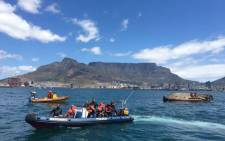 Police divers rescue crew members of a capsized boat in Table Bay. Picture: NSRI Table Bay.