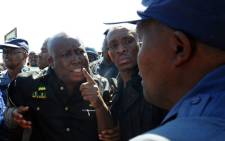 Julius Malema being escorted out of Marikana by police.