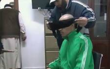 A screengrab from a video which shows Saadi Gaddafi being blindfolded and beaten by guards.