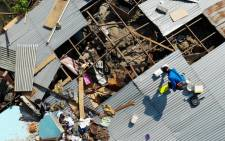 Survivors salvage usable items from the debris of a destroyed house in Palu, Indonesia's central Sulawesi on 2 October 2018, after an earthquake and tsunami hit the area on 28 September. Picture: AFP.