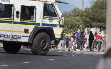 People run away as a South African Police Services armoured vehicle drives into a street during clashes with residents of Tafelsig, an impoverished suburb in Mitchells Plain, near Cape Town, on 14 April 2020, after some people in the community did not receive food parcels which were being handed out as part of the support for this community during the nationwide lockdown to curb the spread of the COVID-19 coronavirus. Picture: AFP