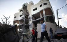 Palestinians walk past the house of senior Hamas official Mahmud al-Zahar after it was destroyed by an overnight Israeli air strike, on 16 July, 2014, in Gaza City. Picture: AFP.