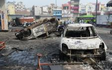 Local residents look at burnt-out vehicles following clashes between people supporting and opposing a contentious amendment to India's citizenship law, in New Delhi on 26 February 2020. Picture: AFP