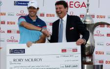 Rory McIlroy of Northern Ireland (L) holds a check with Jonathan Morris, the General Manager of Emirates NBD Bank, after winning the final round of the 2015 Omega Dubai Desert Classic on 1 February, 2015 in Dubai, United Arab Emirates. Picture: AFP