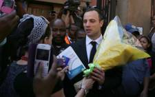 Oscar Pistorius receives a bunch of flowers outside the High Court in Pretoria on 11 April 2014. Picture: Sebabatso Mosamo/EWN.