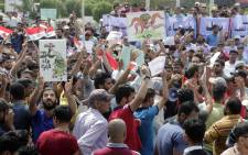 Iraqis shout slogans and hold placards during a demonstration to demand a solution to the long-running problem of salty tap water on 1 August, 2015 in the southern Iraqi city of Basra. Picture: AFP.