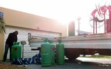 """Department of Fisheries and SAPS begin loading a truck with abalone processing equipment in Sunset Beach. Graeme Raubenheimer/EWN"
