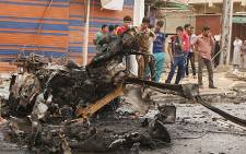 Iraqis look at the remains of a car bomb that detonated in the Kamaliya area of eastern Baghdad on 20 May 2013. Picture: AFP