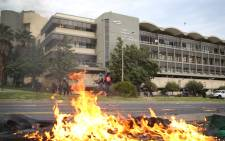 FILE: A plastic bin set alight during student protests burns as private security secure CPUT's Cape Town campus. Photo: Bertram Malgas/EWN