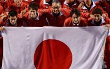Japan team captain Minoru Ueda (C) and players (from L) Yuichi Sugita, Kei Nishikori, Go Soeda and Yasutaka Uchiyama, pose behind the national flag with other team officers on 2 February, 2014. Picture: AFP.