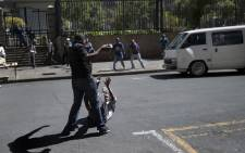 FILE: A local taxi driver pelts with stones a man on the ground during a confrontation with foreign nationals in the Johannesburg Central Business District on 15 April, 2015. Picture: AFP.