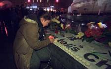 A mourner lights a candle in remembrance of the victims of the Paris terror attacks. Picture: Supplied/EWN.