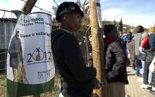 A woman stands near an election poster in Maseru on 24 May 2012. Picture: AFP