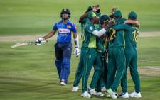 Sri Lanka's Kusal Mendis (L) walks back to the pavilion after being run out by South Africa's wicketkeeper Quinton de Kock (C/obscured by celebrating teammates) during the second one day international (ODI) cricket match between South Africa and Sri Lanka at The Supersport Stadium in Pretoria on 6 March 2019. Picture: AFP