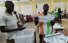 FILE: An official of Ivory Coast's Independent Electoral Commission (IEC) holds a ballot as votes are counted in Abidjan after polls closed in Ivory Coast's presidential election. Picture: AFP.