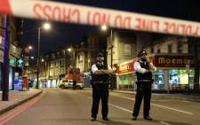FILE: Police officers guard a cordon, set up on Streatham High Road, at the junction of Prentis Road, in south London on 2 February 2020. Picture: AFP