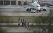 Members of Malta's Armed Forces check the runway after a small passenger aircraft crashed on takeoff at Malta's international airport on 24 October 2016, killing all five people onboard, officials said.  Picture: AFP.