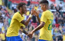 Brazil's striker Roberto Firmino (R) celebrates with Brazil's striker Neymar after scoring their second goal during the International friendly football match between Brazil and Croatia at Anfield in Liverpool on 3 June 2018. Brazil won the game 2-0. Picture: AFP