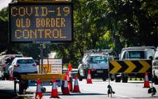 This file photo taken on 15 April 2020 shows a COVID-19 coronavirus sign at a Pacific Highway vehicle checkpoint on the Queensland-New South Wales state border near Coolangatta. Picture: AFP