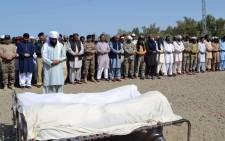 This handout photograph released on 11 April, 2015, by Pakistan's Press Information Department (PID) shows Pakistani government and security officials offering funeral prayers for construction workers killed in an attack by gunmen in Turbat in the southwestern province of Baluchistan. Picture: AFP.