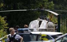 This picture taken on 1 July 2018 in Gonesse, north of Paris shows police near a French helicopter Alouette II abandoned by French armed robber Redoine Faid after his escape from prison in Reau. Picture: AFP.