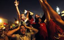 Egyptian protesters calling for the ousting of President Mohamed Morsi react as they watch his speech on a screen in a street leading to the presidential palace early in Cairo on 3 July, 2013. Picture: AFP/ Mahmud Khaled