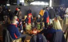 Corporate executives trying to keep warm around a fire as temperatures drop. Picture:Kgothatso Mogale/EWN