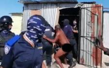 A screengrab from a video taken on 1 July 2020 in which Cape Town law enforcement officials evict a naked man from his Empolweni home in Khayelitsha.