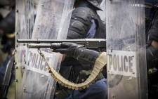 FILE: Through riot shields, a police officer fires rubber bullets at students during clashes with students at the University of the Western Cape. Picture: Thomas Holder/EWN.