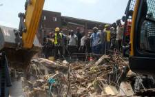 Emergency and rescue personnel are seen at the site of a building which collapsed in Lagos on 13 March 2019. At least 10 children were among scores of people missing on 13 March 2019 after a four-storey building collapsed in Lagos, with rescuers trying to reach them through the roof of the damaged structure. Picture: AFP