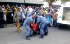 FILE: A screenshot of the video in which Mozambican taxi driver Mido Macia is dragged behind a police van in Daveyton, later dying in a cell, February 2013. Picture: Daily Sun/YouTube.