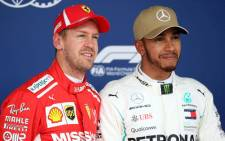 Second place qualifier Sebastian Vettel and Ferrari and pole position qualifier Lewis Hamilton of Mercedes GP pose for a photo in parc ferme during qualifying for the United States Formula One Grand Prix at Circuit of The Americas on 20 October, 2018 in Austin, United States. Picture: AFP