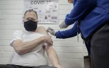 FILE: Professor Martin Veller (L), the Dean of the Faculty of Health Sciences at the University of the Witwatersrand (Wits University), receives an experimental vaccine for COVID-19 coronavirus at the Respiratory & Meningeal Pathogens Research Unit (RMPRU) at Chris Hani Baragwanath Hospital in Soweto on 14 July 2020. Six senior clinicians in the Faculty of Health Sciences at Wits University have volunteered to participate in South Africa's first COVID-19 vaccine trial. Picture: AFP