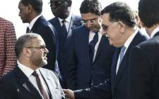 The head of the UN-backed unity government in Tripoli, Prime Minister Fayez al-Sarraj (R) talks with President of the High Council of State of Libya Khaled Mechri (L) as they pose for a group photo on 13 November 2018 during an international conference on Libya at Villa Igiea in Palermo. Picture: AFP