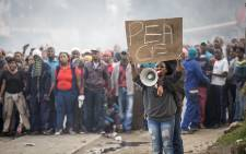 "During a cease-fire between police and rioting residents of Masiphumelele township, Cape Town, a resident holds up a sign with ""Peace"" inscribed on it. At this point, residents were looking to negotiate a permanent solution to the violence. Picture: Thomas Holder/EWN"