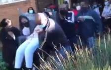 Screengrab of a video showing a group of parents carrying Laerskool Theresapark principal Dorothy Mabaso with her office chair out of the administration office, before she falls off the chair. Picture: Screengrab